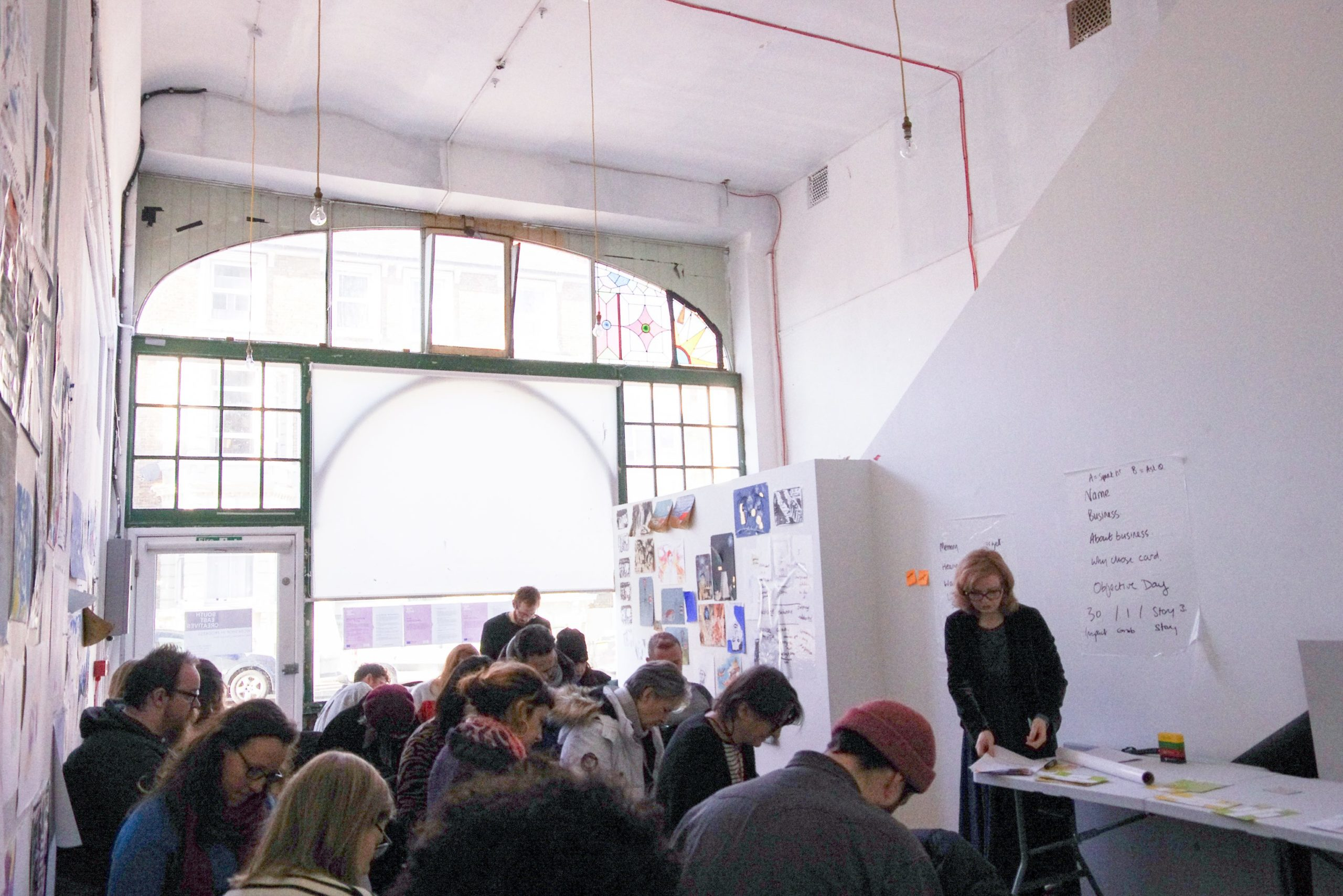 a lve workshop taking place in a large light flooded space with many old windows